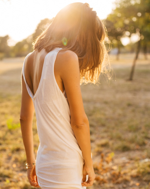Woman standing in field with sunlight on her