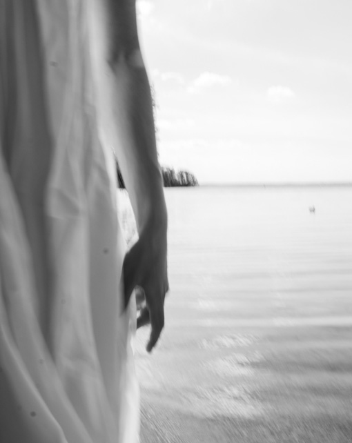 Black and white abstract abstract photo of woman standing in front of water in long white dress